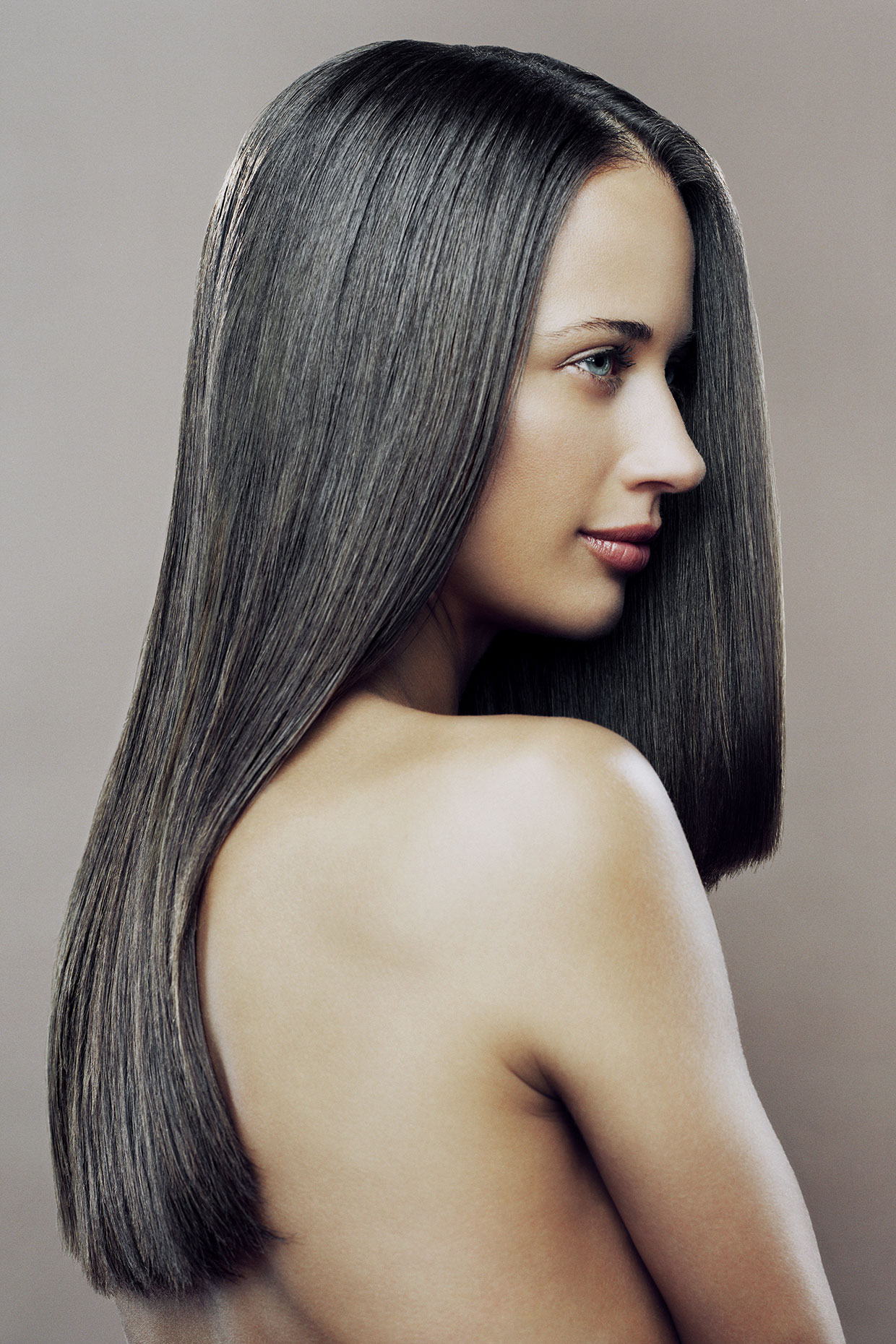 Woman with long, shiny  hair in a profile position.