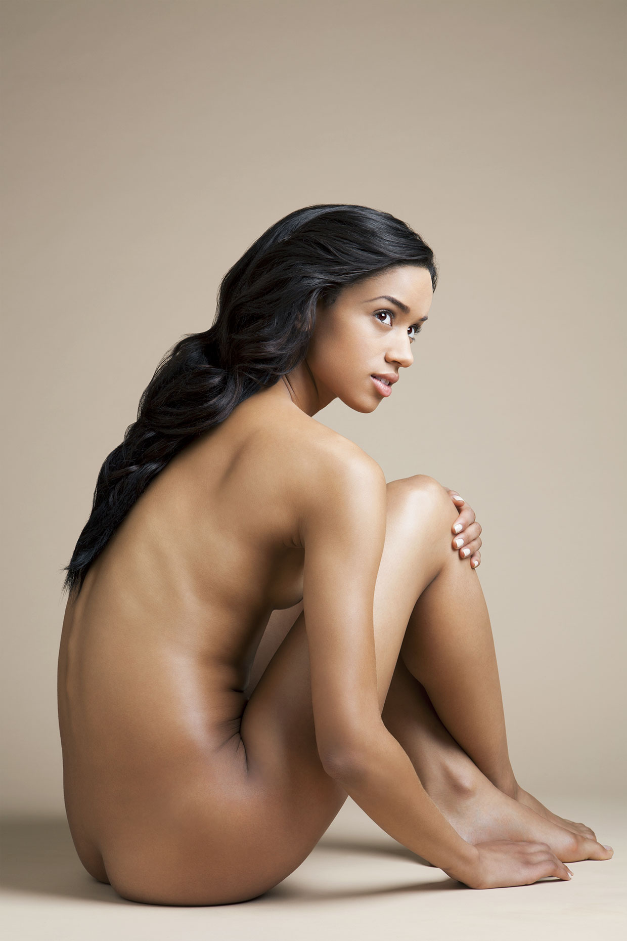 Nude young woman sitting in profile position.