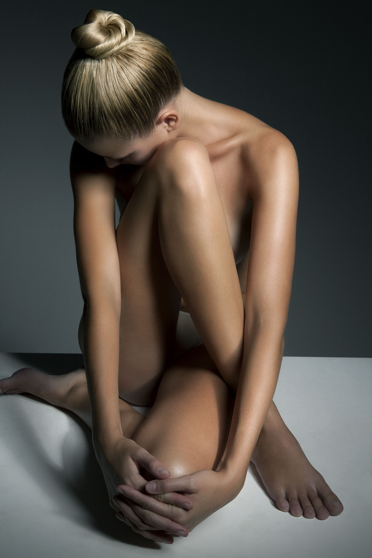 Naked woman with shiny hair do sitting, side view.