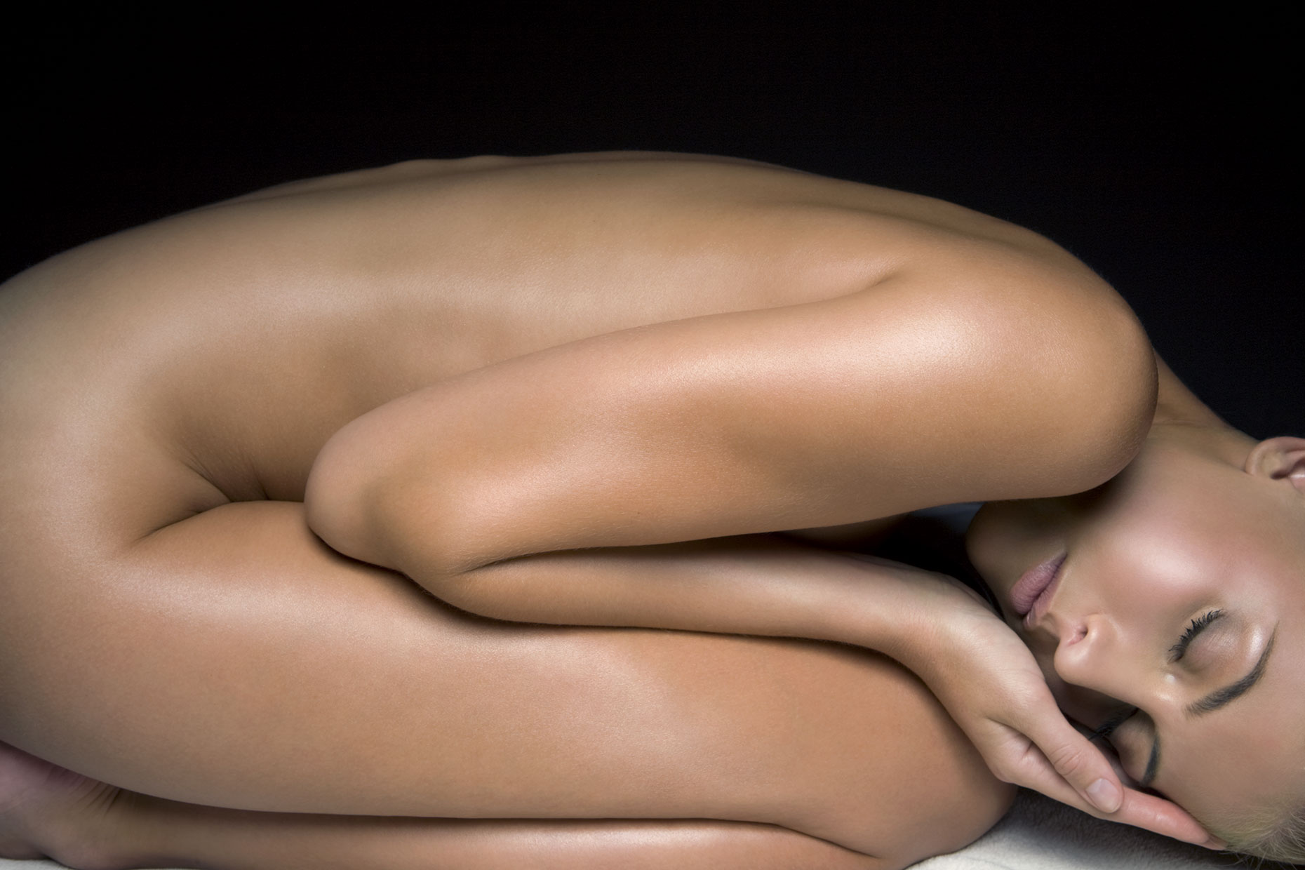 Naked young woman in fetal position, side view.