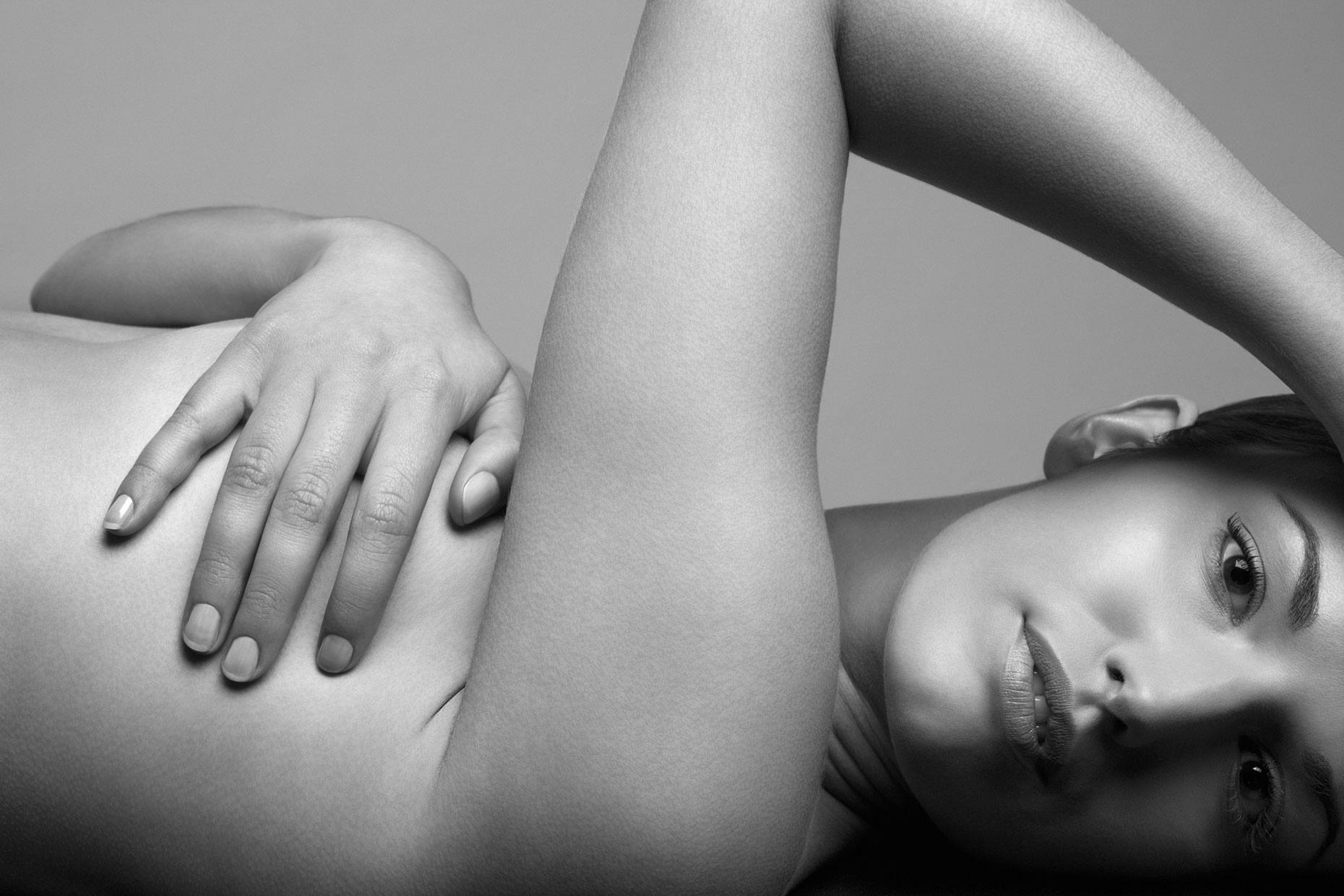 Nude young woman covering breast laying down.