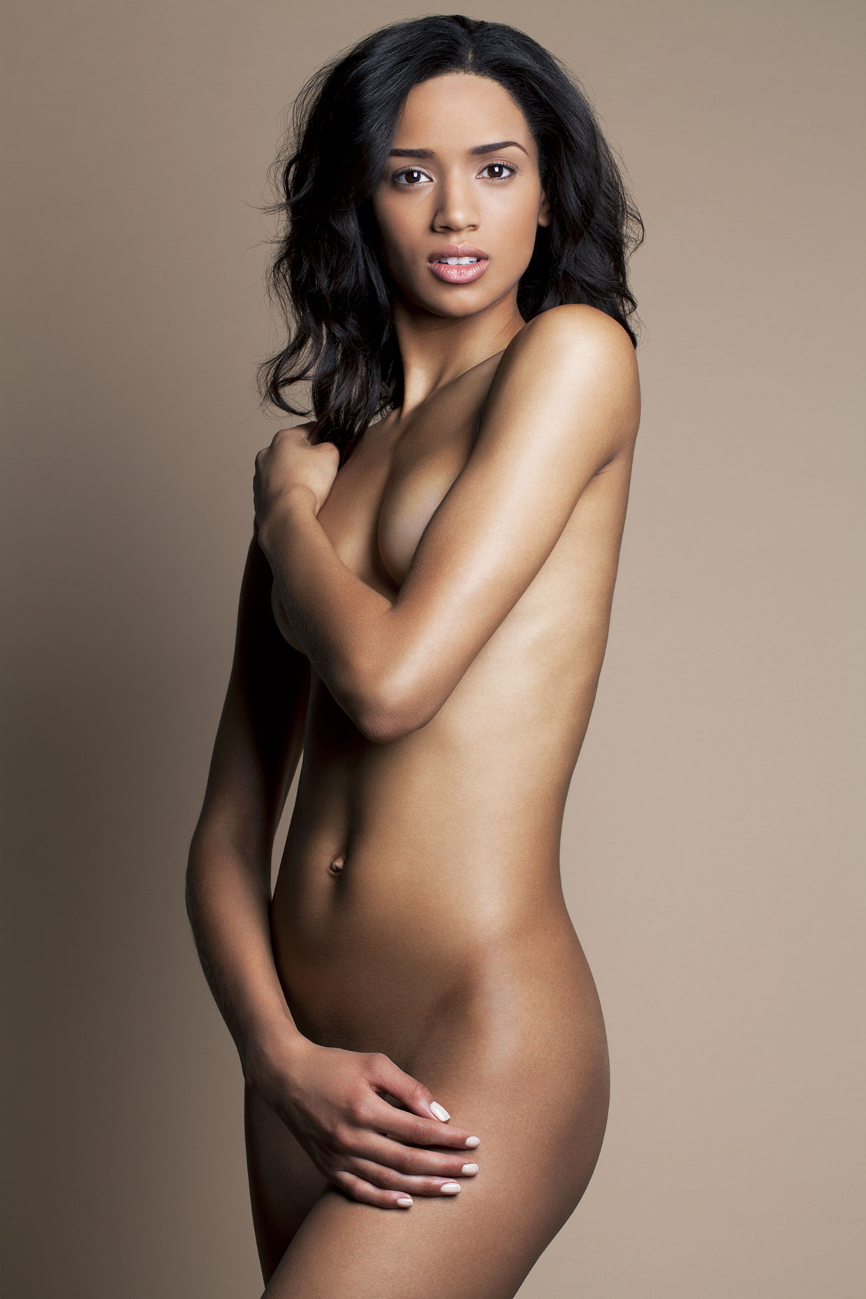 Nude young African American woman covering up with her arms.