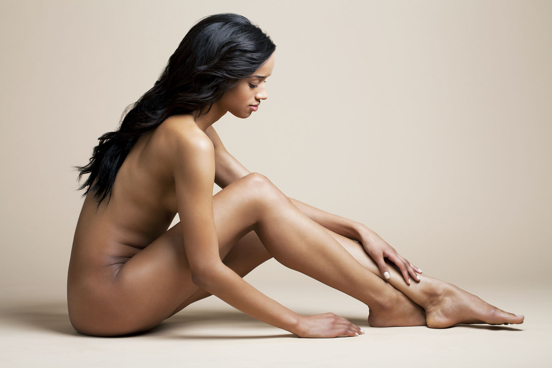 Nude young woman sitting while touching her leg.