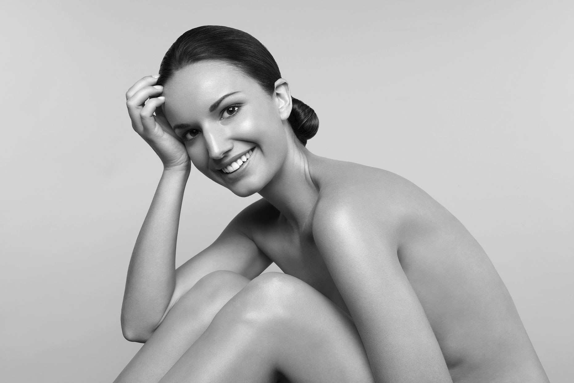 Smiling nude young resting head on hand.