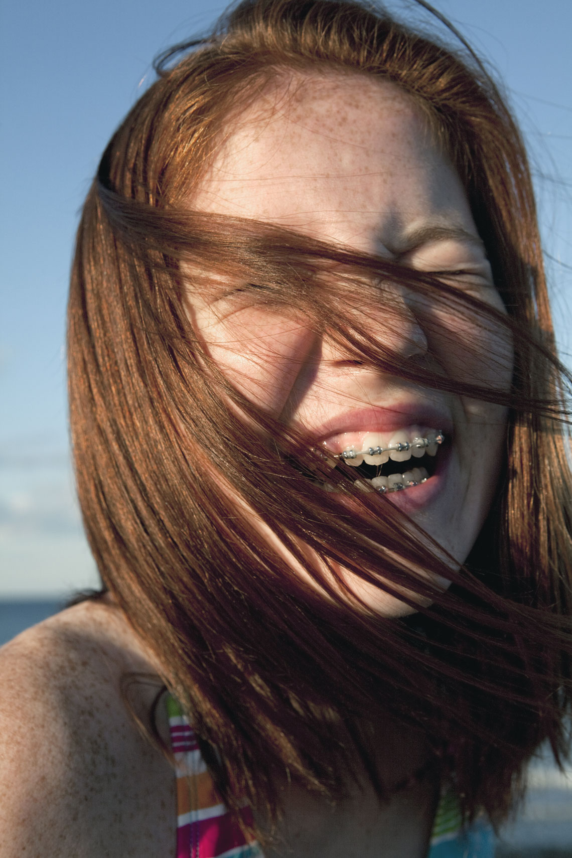 Teenage girl with braces laughing, portrait.