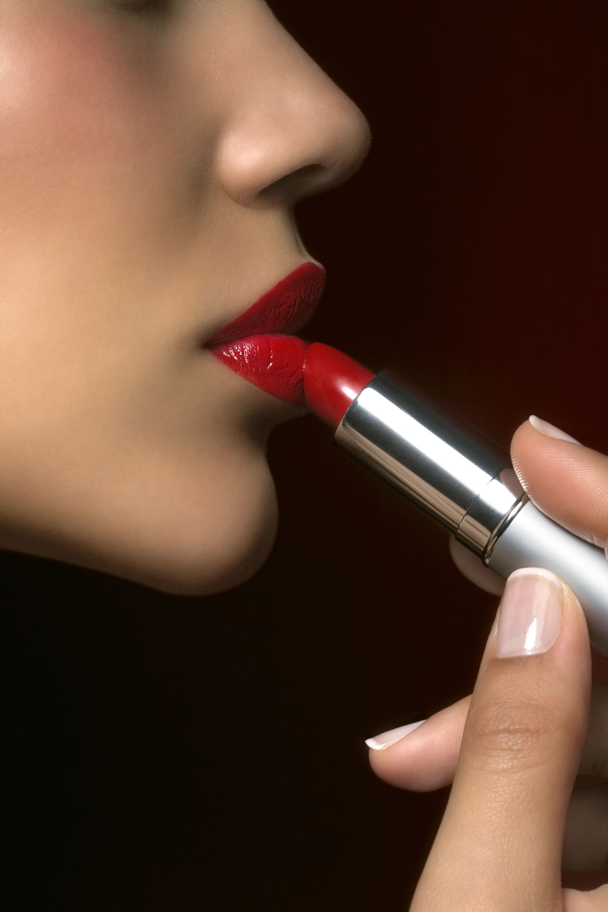 Young woman applying lipstick, close-up