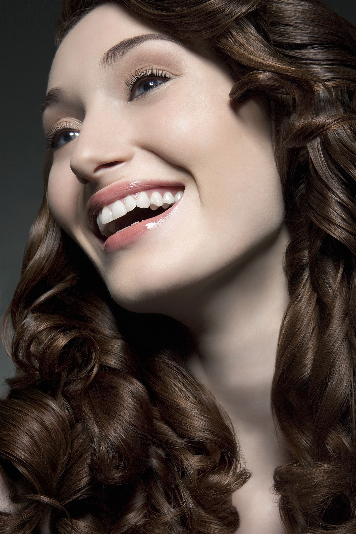 Young woman with shiny hair laughing, portrait.