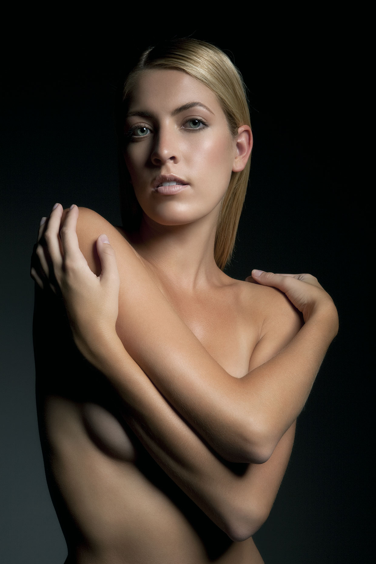 Naked young woman crossing her arms, portrait.