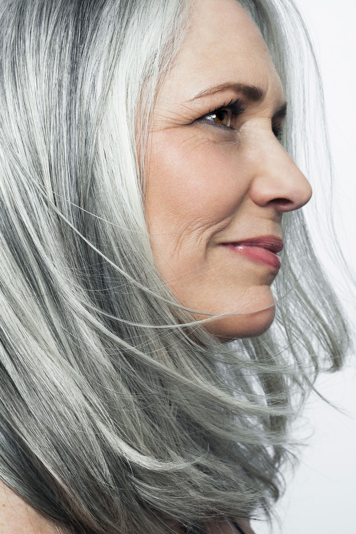 Grey haired woman with a soft smile, profile.