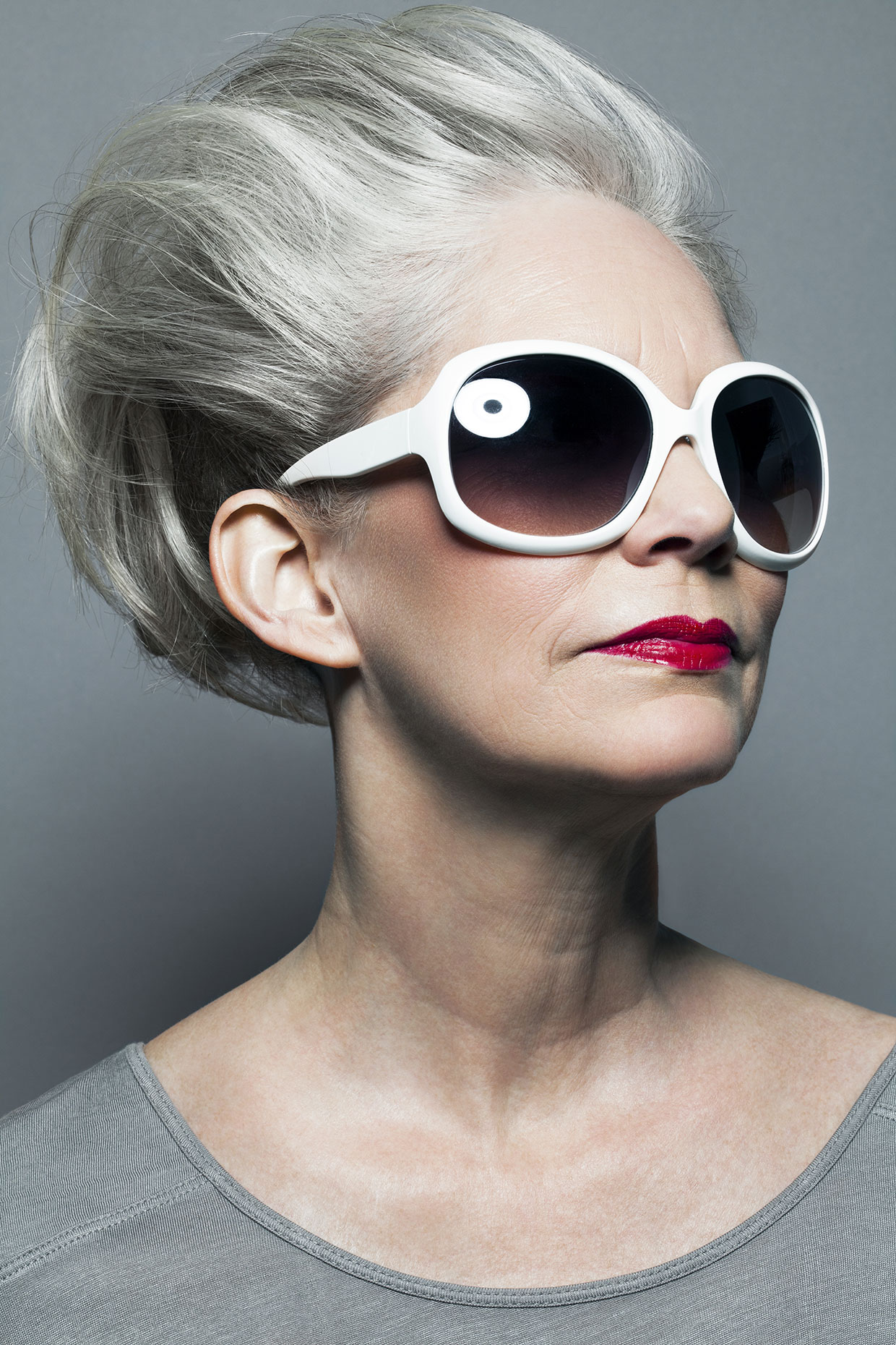 Mature woman with silvery, gray hair and red lipstick and sunglasses.