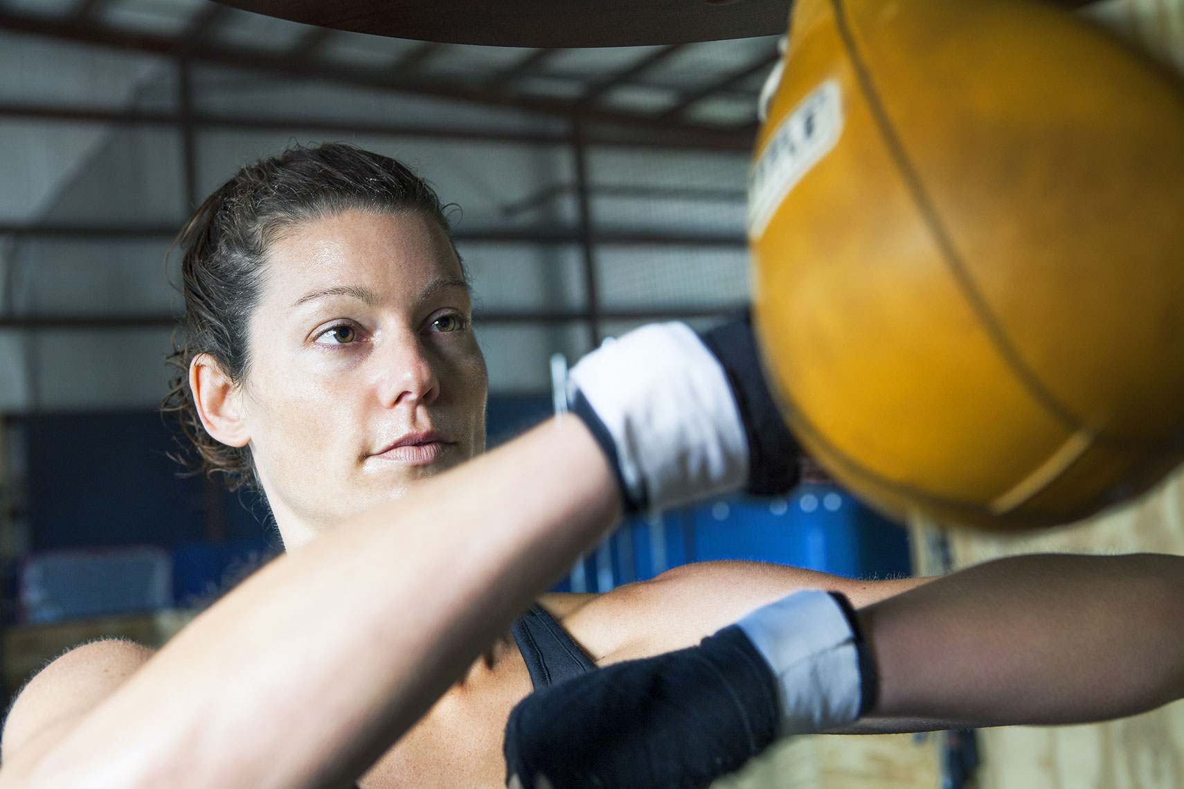 Young woman doing a speed bag boxing workout.