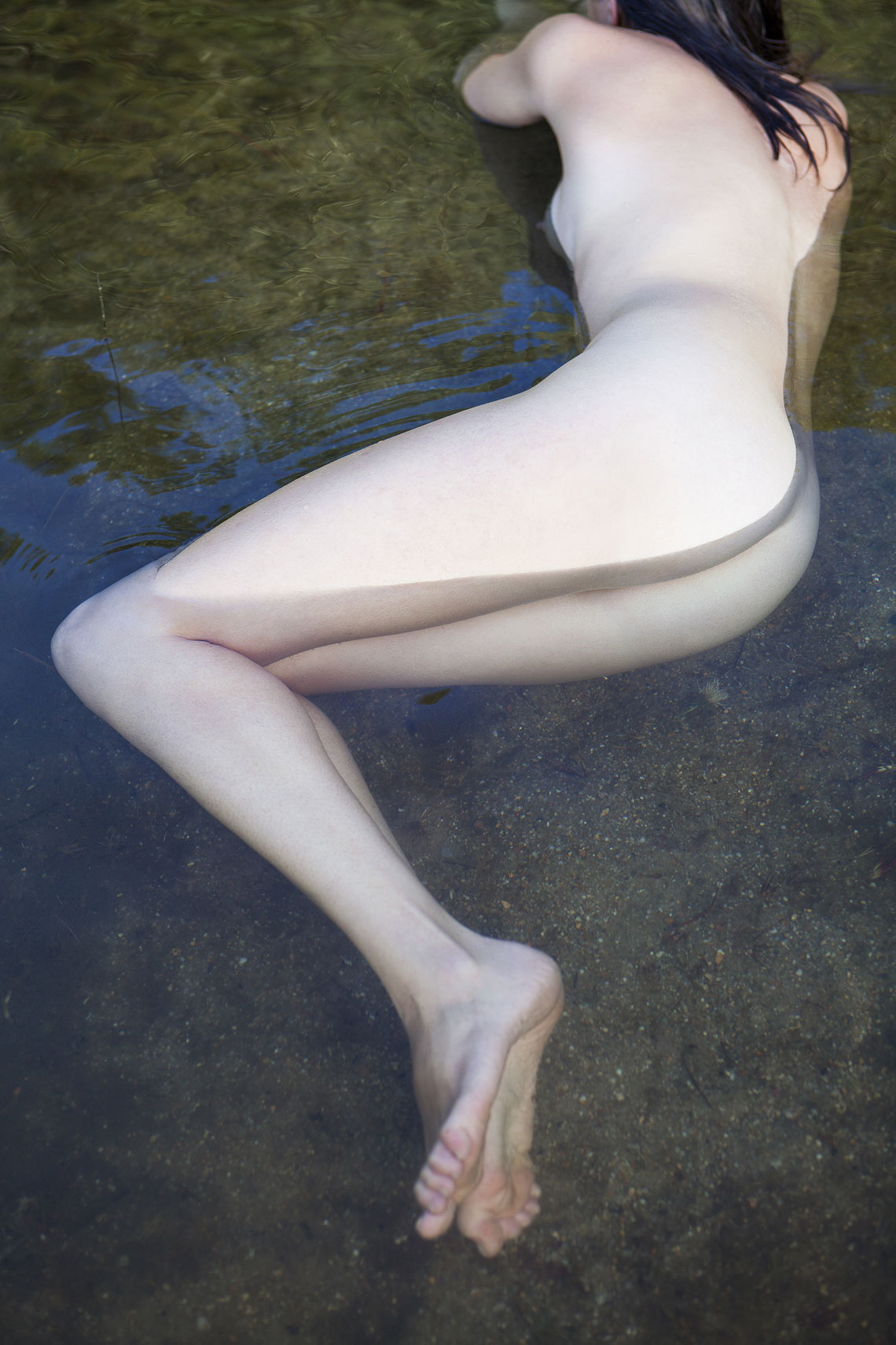 Naked woman almost submerged by water in a pond.