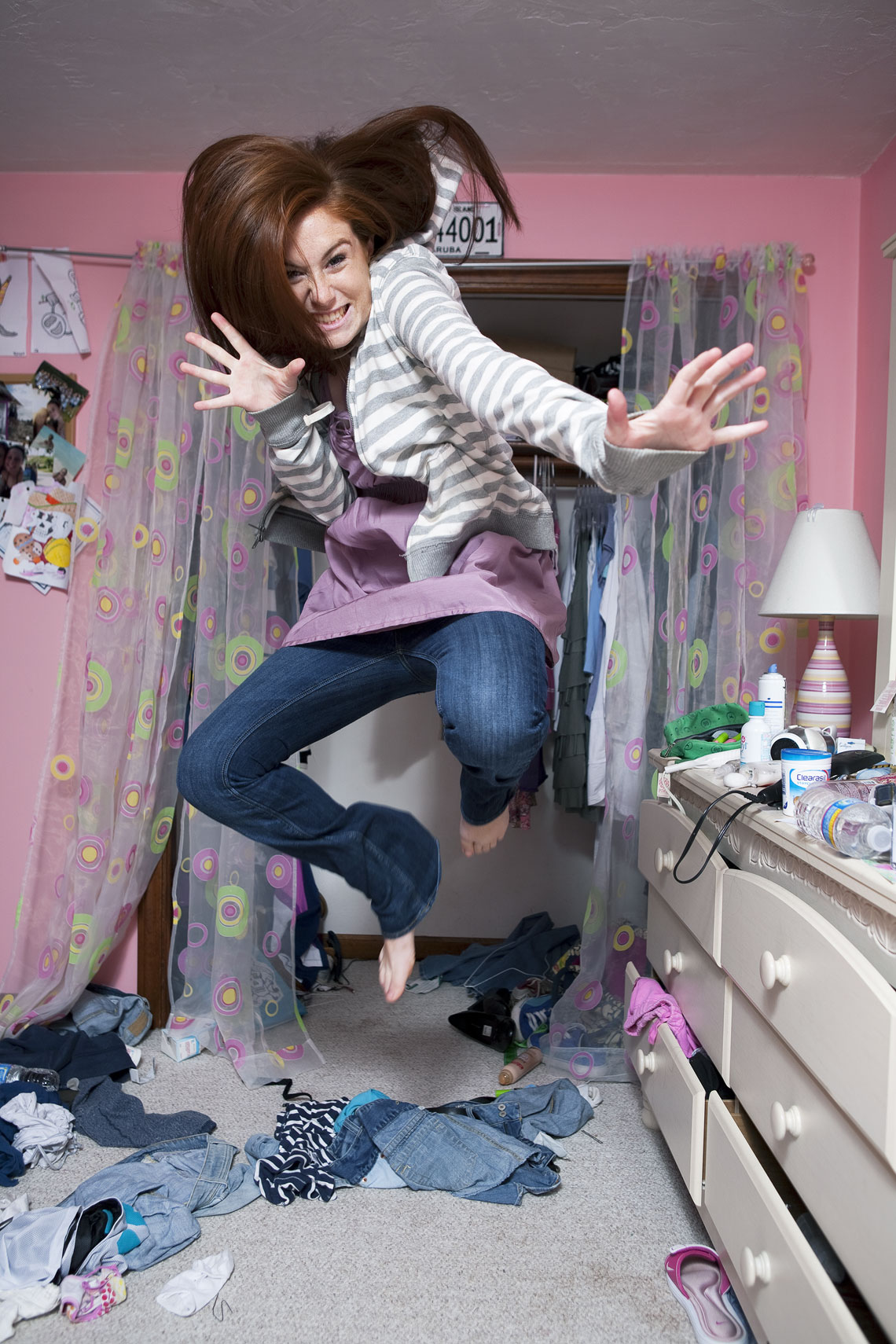 Teenage girl jumping in her messy room.