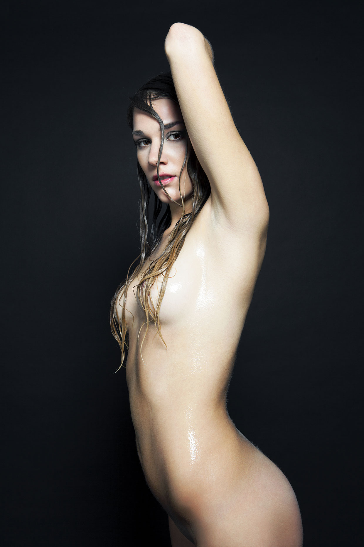 Wet and nude young woman standing, 3/4 length.