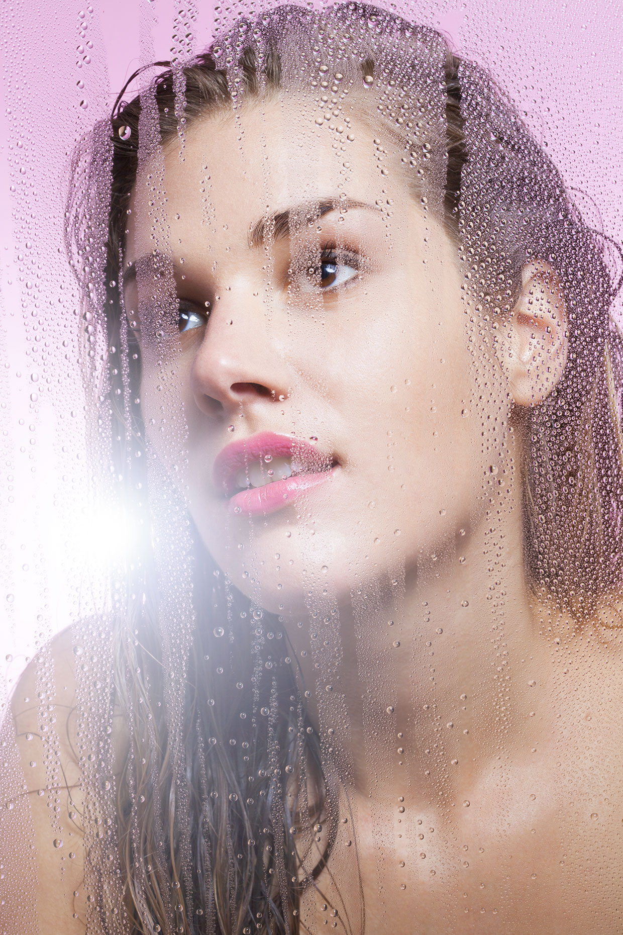 Young woman behind glass with water droplets.