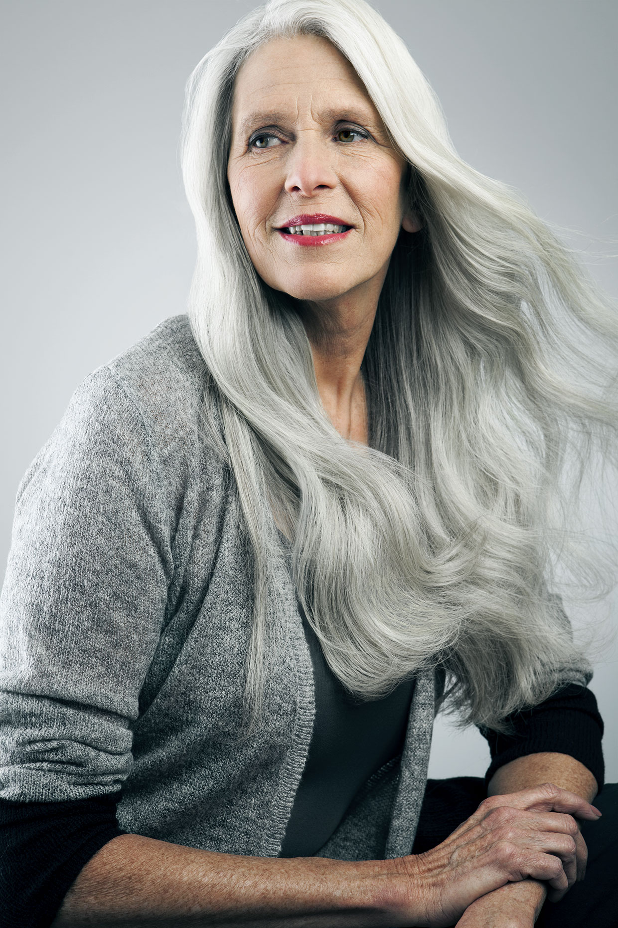Mature woman with long, gray hair looking away.