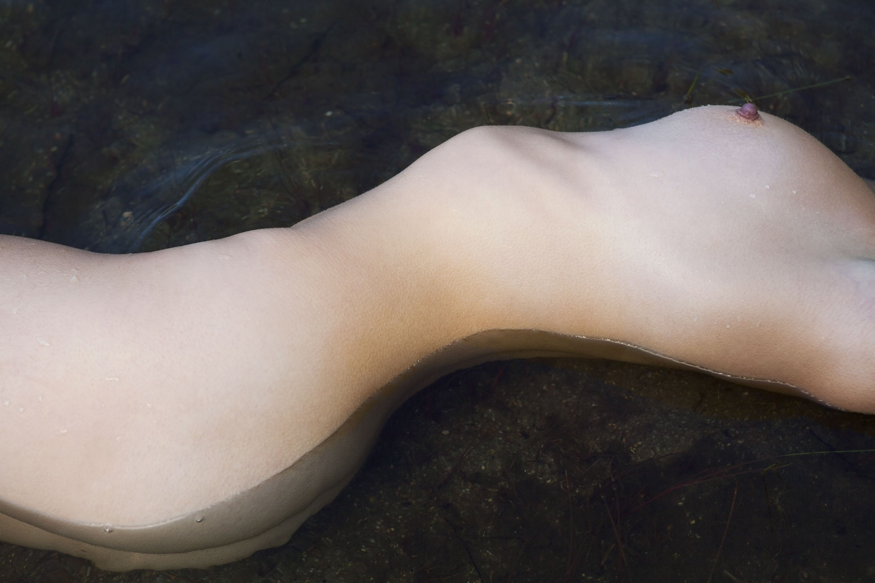 Torso of naked woman in water, side view.