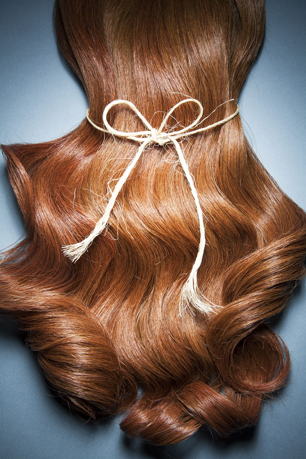 Close up of shiny wavy,  red hair with a string around it.